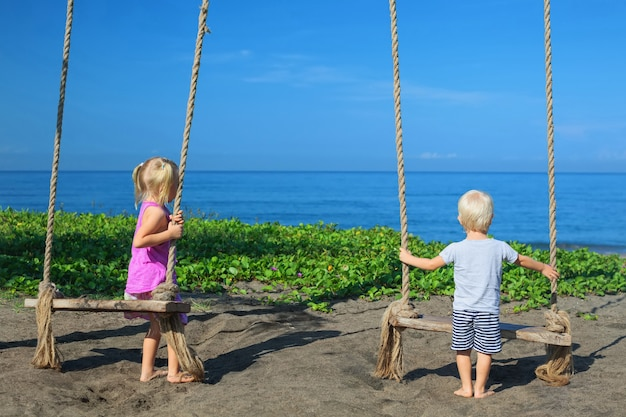 Caucasian little kids - girl and boy have fun together on rope swing at black sand beach on summer family vacation.
