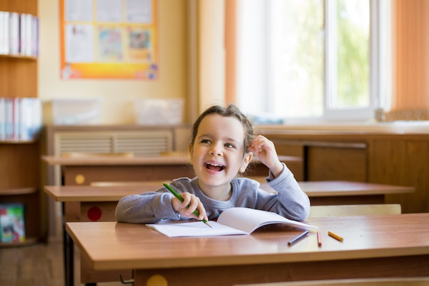 Caucasian little smiling girl sitting at desk in class room and begins to carefully draw in a pure notebook.
