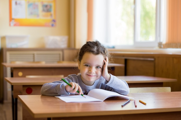 Caucasian little smiling girl sitting at desk in class room and begins to draw in a pure notebook