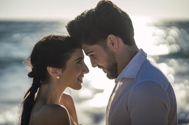 Кавказская влюбленная пара в белой одежде и обниматься на пляже во время свадебной фотосессии