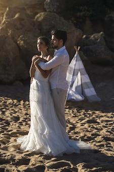 Coppie amorose caucasiche che indossano vestiti bianchi e che abbracciano in spiaggia durante un servizio fotografico di matrimonio
