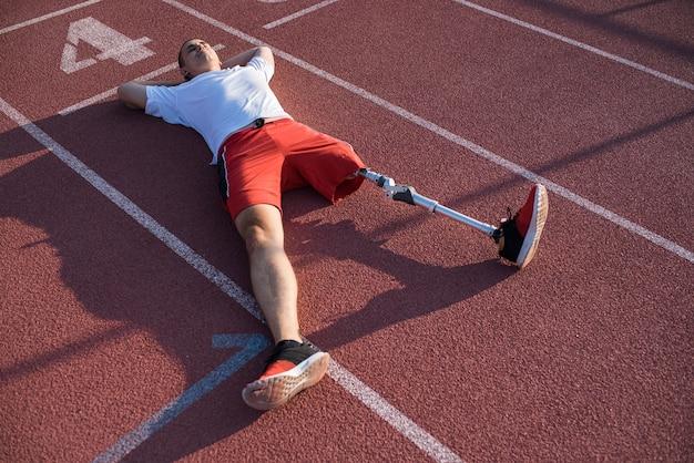 スタジアムの線路に横になっている義足を持った白人男性アスリート。スポーツのコンセプト。