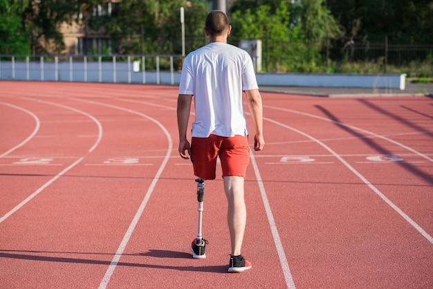 スタジアムのトラックを歩いている足に義足を持った白人男性アスリート。背面図。スポーツのコンセプト。