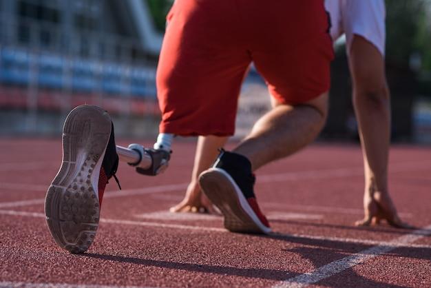 スタジアムのトラックのスタート地点に義足が立っている白人男性アスリート。背面図。スポーツのコンセプト。