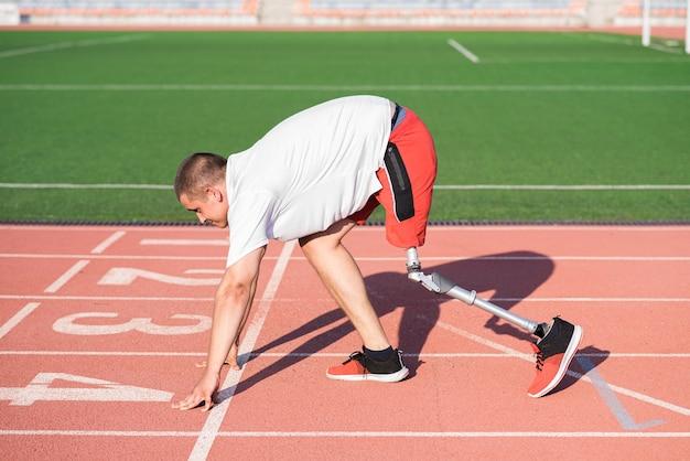 スタジアムのトラックのスタート地点に義足が立っている白人男性アスリート。スポーツのコンセプト。