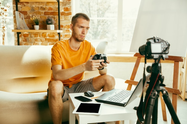 Caucasian male blogger with camera recording video review of gadgets at home
