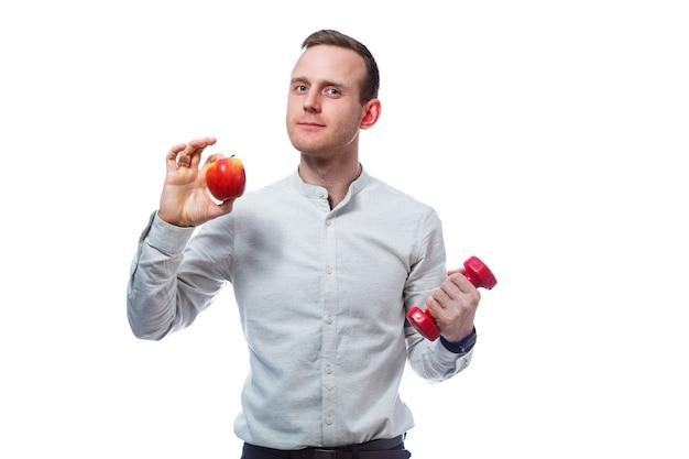 빨간색-노란색 사과와 빨간색 아령을 들고 백인 남성 사업가. 그는 셔츠를 입고 있다. 감정적인 초상화입니다. 흰색 배경에 고립