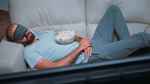 Кавказский мужчина засыпает во время просмотра фильма, сидя на диване