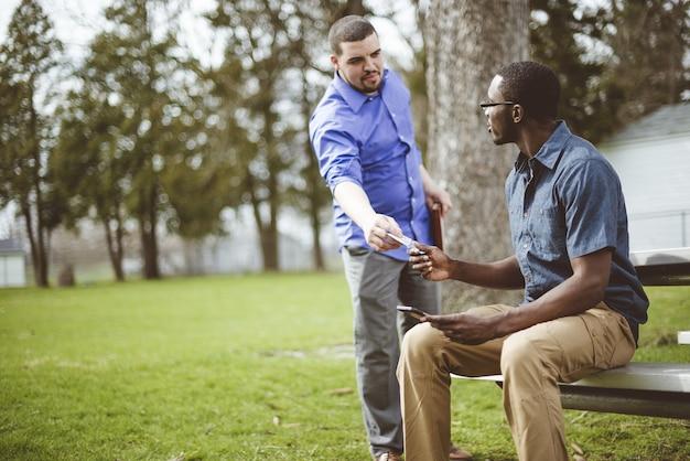 公園でアフリカ系アメリカ人の男性にメモを与える白人男性