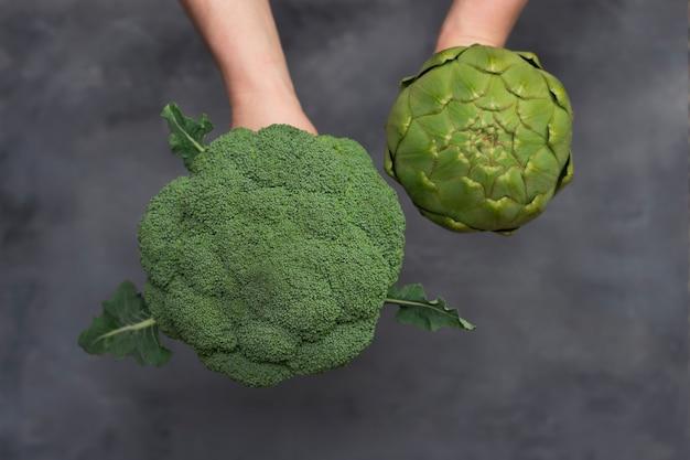 브로콜리와 회색 표면에 고립 된 녹색 아 티 초 크를 들고 백인 남성 손.