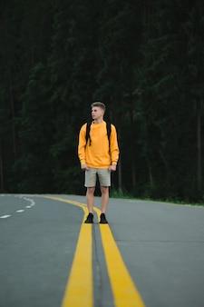 山の森の道の真ん中に立っている白人男性ハイカー観光客