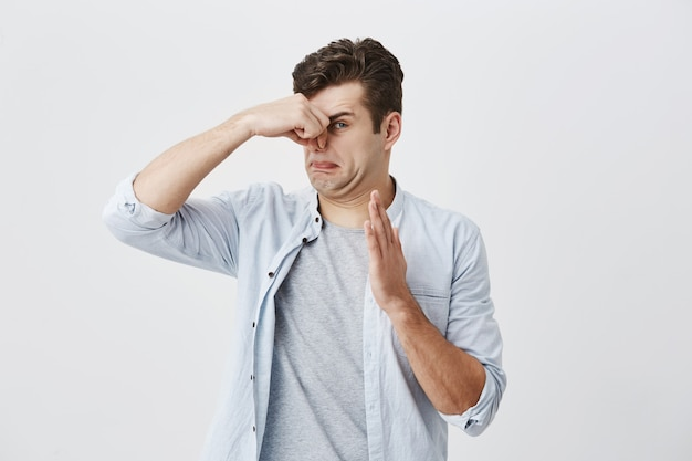 Caucasian male hipster with dark hair dressed in light blue shirt over gray t-shirt pinching nose because of bad smell of something dirty and stinky, looking  with disgusted expression.