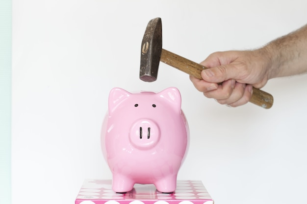 Caucasian male holding a hammer and about to break a piggy bank