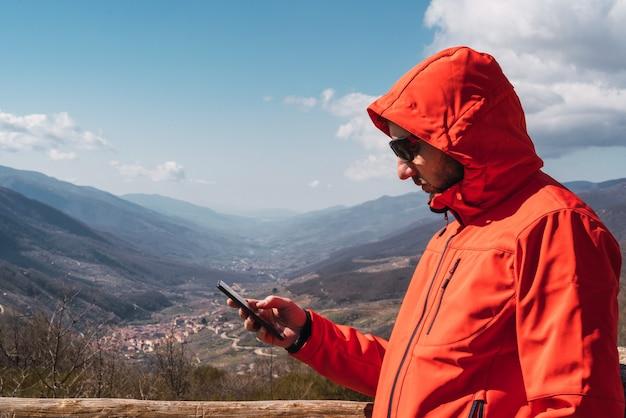 Кавказский мужчина в красном пальто печатает со своим смартфоном на фоне гор и голубого неба с облаками