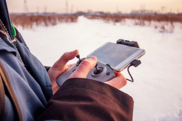 冬のフィールドで彼の手にリモコンで飛んでいるドローンを起動する青いジャケットの白人男性。
