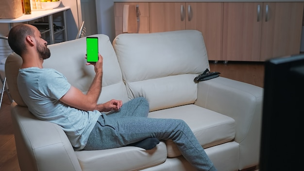 Caucasian male looking phone with at mock up green screen chroma key display