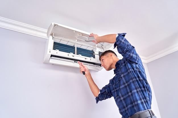 青いシャツを着た白人男性のマスターは、フィルターを掃除し、エアコンを屋内に設置して修理します