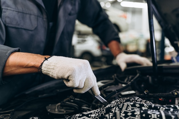 백인 남성 정비사가 차고에서 차를 수리합니다. 자동차 정비 및 자동 서비스 차고 개념입니다. 근접 촬영 손과 스패너