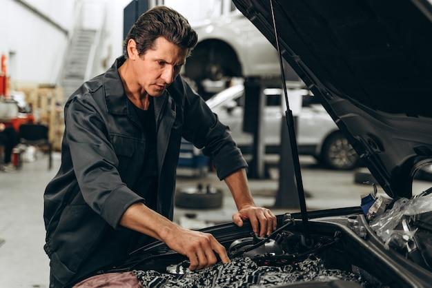 백인 남성 정비사가 차고에서 차를 수리합니다. 주의 깊게 차를 보고 있는 남자. 자동차 유지 보수 및 자동 서비스 차고 개념