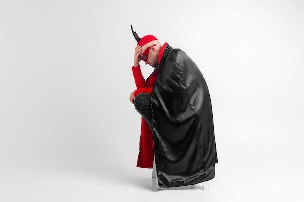 Кавказская мужская модель в черном красном костюме хэллоуина и солнцезащитных очках с шляпой и рогами, позирует на белом фоне.