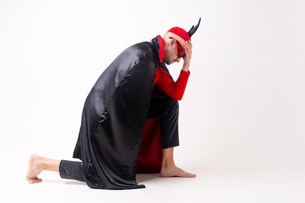 白の上にポーズをとる帽子と角を持つハロウィーンの黒赤の衣装とサングラスの白人男性モデル。