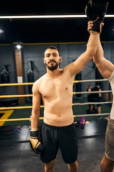 Caucasian male putting up his left arm above his head after winning a sparring match