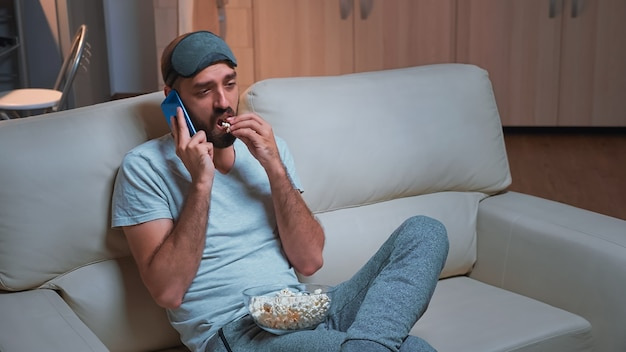 Кавказский мужчина отдыхает на диване, ест попкорн, разговаривая по телефону с другом о социальной сети. мужчина relasex сидит перед телевизором и смотрит развлекательное шоу поздно ночью на кухне