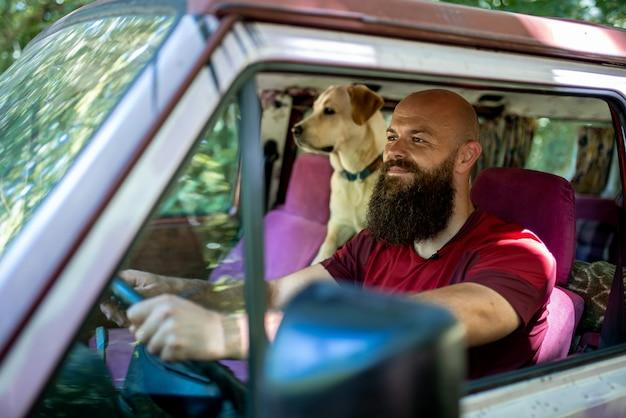 Maschio caucasico in sella alla sua auto con il suo golden retriever