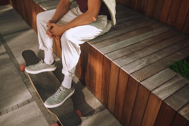 トレーニング後に休んでいる白人男性のスケートボーダー