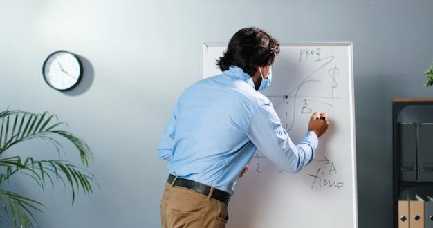 Кавказский учитель-мужчина в медицинской маске и очках стоит за доской в классе и говорит классу законы физики или геометрии. концепция пандемии. школа во время коронавируса. учебная лекция.