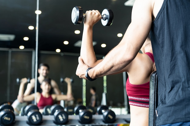 Caucasian male trainer helping young asian female workout on shoulder muscle by lifting dumbbells on both arms in gym or fitness club.