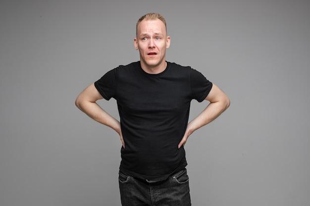 회색 벽에 고립 된 벨트에 손으로 포즈 검은 티셔츠와 청바지를 입고 백인 남성