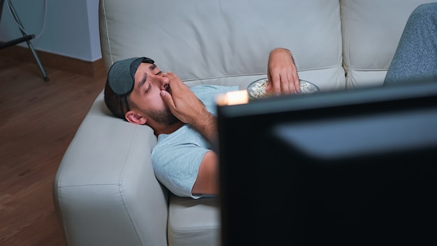 Caucasian male with eye sleep mask eating popcorn while watching entertainment tv show