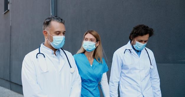 一緒に歩いて元気に話している医療用マスクの白人男性と女性医師の同僚。 2人の男性と女性、医師が足を踏み入れて仕事についておしゃべりします。保護されています。医者が働いています。