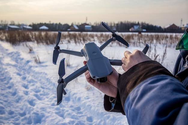 Caucasian man of 30 years flying drone in snowy field in winter.