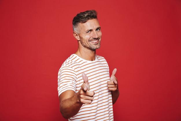 Кавказский мужчина 30-х годов в полосатой футболке показывает указательным пальцем на камеру, что означает: эй, ты изолирован на красном