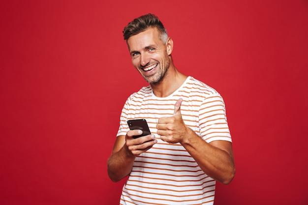 赤で隔離の携帯電話を笑顔で保持している縞模様のtシャツを着た白人男性30代