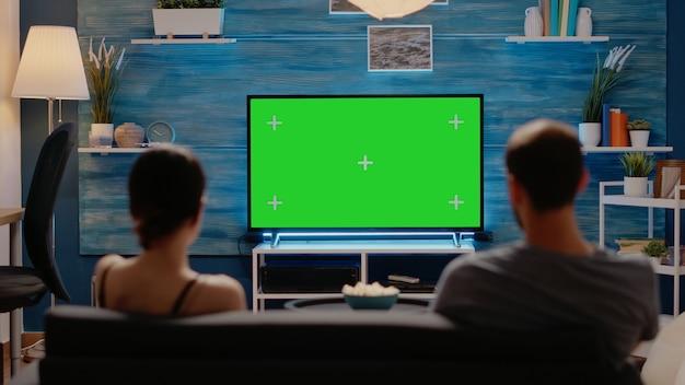 緑の画面を見ている白人の男性と女性
