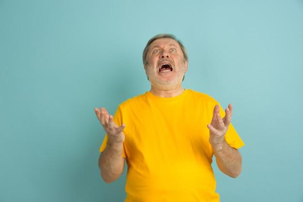 Uomo caucasico arrabbiato che grida in su isolato sull'azzurro