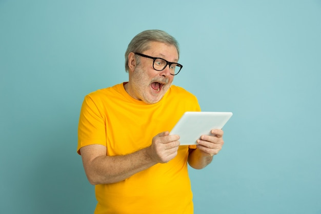 Caucasian man astonished using tablet isolated on blue