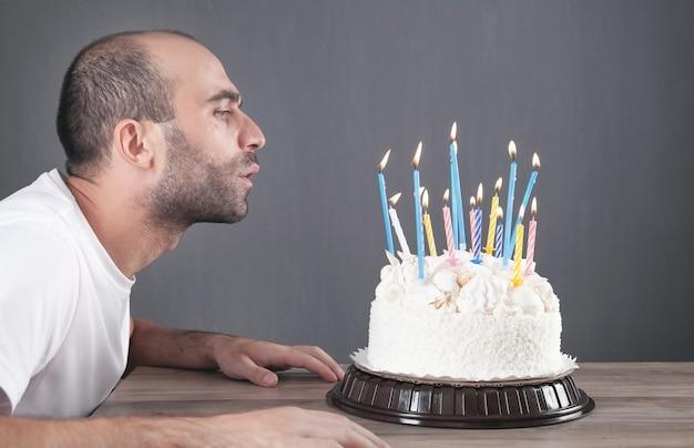 誕生日のロウソクを吹く白人男性。