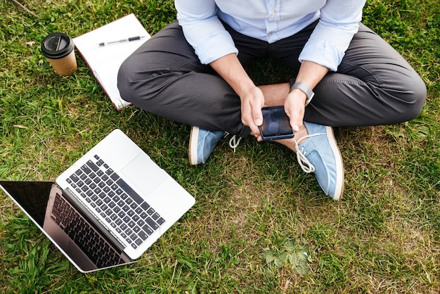 Caucasian man in business clothing, sitting on grass in park while using cell phone and silver laptop