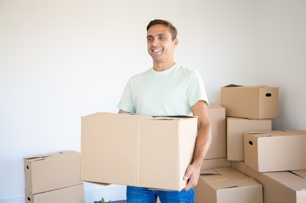 Caucasian man carrying carton box in his new house or apartment