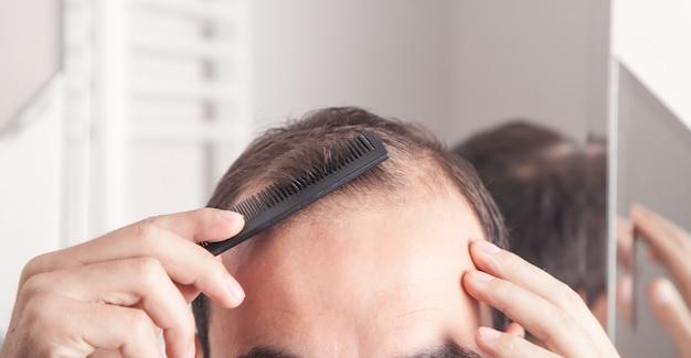 Кавказский мужчина расчесывает волосы.