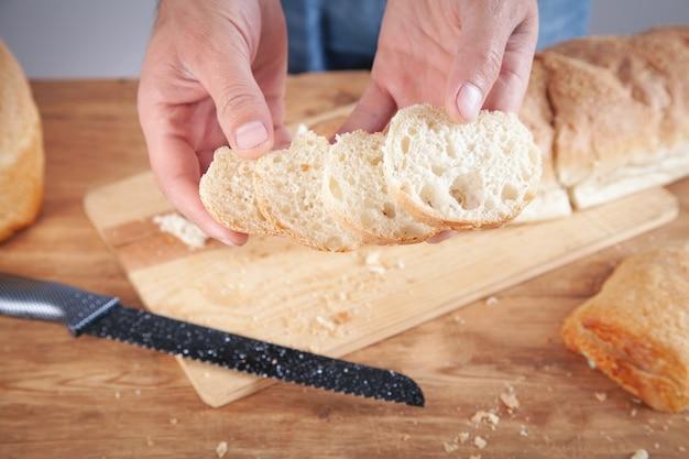 パンを切る白人男性。健康食品