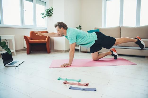 Кавказский мужчина делает фитнес-упражнения перед ноутбуком во время онлайн-уроков фитнеса