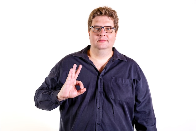 흰 벽에 고립 된 그의 손으로 긍정적 인 백인 남자