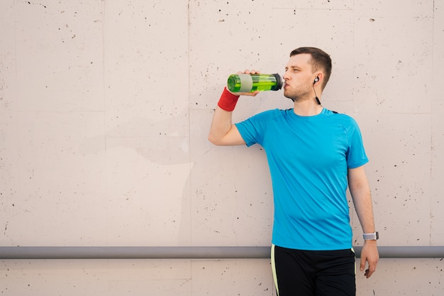 Caucasian man drinking water during exercises