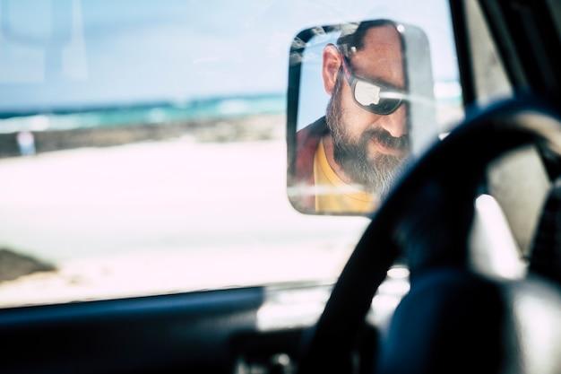 車の鏡で見たサングラスをかけた白人男性の顔