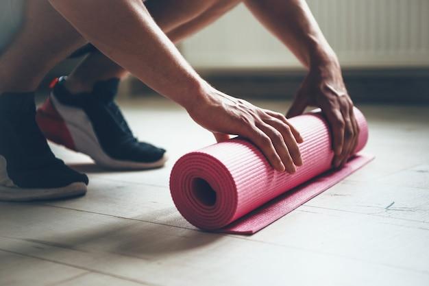 Кавказский мужчина заканчивает делать упражнения, собирает свой ковер для йоги с пола